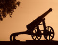 Black silhouette of the old gun cannon is photographed against sky at sunset Stock Image