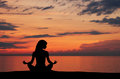 A black silhouette of a woman doing yoga on a sunset Stock Photography