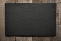 Black slate tile on wooden background. Top view. Royalty Free Stock Photo