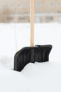 Black snowshowel with wooden handle in snow pile Stock Photo