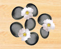 Black spa stones and white spring flowers over yellow wooden Royalty Free Stock Photo