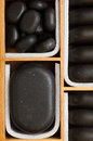 Black spa zen massage stones in wooden case as background beauty salon close up of relax concept Royalty Free Stock Photo