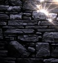 Black stone wall with bright lights in the top right corner Stock Photography