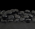 Black stones on calm water background Royalty Free Stock Photography
