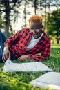 Black student in glasses reading book on the grass Royalty Free Stock Photo