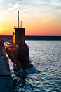 Black submarine in port in the sunset Stock Photo