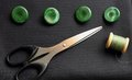 Black suiting fabric, scissors and green buttons Royalty Free Stock Photos