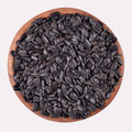 Black sunflower seeds in a wooden bowl on white background Stock Photo