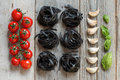 Black Tagliatelle pasta with cherry tomatoes, garlic and basil Royalty Free Stock Photo