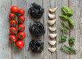 Black Tagliatelle pasta with cherry tomatoes, garlic and herbs Royalty Free Stock Photo