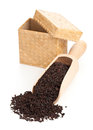 Black tea crop ceylon in wooden scoop over white background Stock Photos