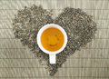 Black tea heart shape topview over bamboo mat with teacup Royalty Free Stock Photography
