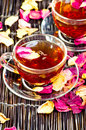 Black tea with roses petals Stock Photos