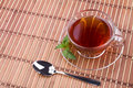 Black tea on table in glass cup with pepper mint and spoon Stock Image