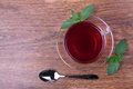 Black tea on table in glass cup with pepper mint and spoon Stock Photos