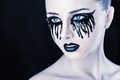 Black tears closeup of a beautiful woman with fantasy makeup with and lips on a background Stock Photography