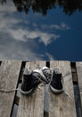 Black teenager's shoes standing on the bridge edge, choice concept Royalty Free Stock Photo