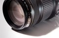 Black telezoom objective on a white acryl plate camera photography lens zoom Royalty Free Stock Photography
