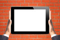 Black touch screen tablet in woman hands over brick wall orange Royalty Free Stock Images