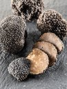 Black truffles and truffle slices on the board. Royalty Free Stock Photo