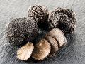 Black truffles and truffle slices on a graphite board. Royalty Free Stock Photo