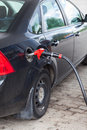 Black vehicle refueling with gasoline at city gas station Royalty Free Stock Photos