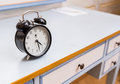 Black vintage alarm clock on a blue table in a hotel room Royalty Free Stock Image