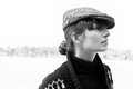 Black and white autumn portrait profile of pretty young woman wearing turtle neck boyish peaked cap sweater looking aside high Stock Image