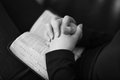 A black and white close up of a christian woman folding hands and praying on the bible shot with canon mm l very shallow depth of Royalty Free Stock Photos