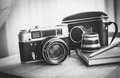 Black and white closeup photo of old camera and notebook on desk Royalty Free Stock Photo