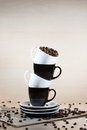 Black and white cups on the stack of the plates with full of roasted coffee beans standing on newspaper. Royalty Free Stock Photo