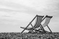 Black and white deck chairs on brighton beach england a low angle monochrome shot of a pair of looking out to sea Stock Image
