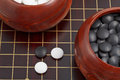 Black and white go game stones and wooden bowls on goban Royalty Free Stock Images