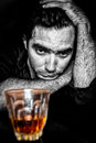 Black and white grunge portrait of a drunk and depressed hispani hispanic man with contrasty golden alcoholic drink Stock Photo