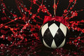 Black white harlequin christmas ornament a hanging patterned in and with red bow red and sparkling bokeh on background Royalty Free Stock Photos