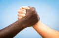 Black and white human hands in a modern handshake against racism to show each other friendship respect arm wrestling Stock Images