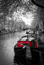 Black and white image of an amsterdam canal with red tug boat