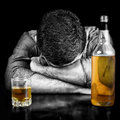 Black and white image of a drunk man sleeping with his head on table bottle whisky the bottle glass have color Royalty Free Stock Image