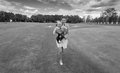 Black and white image of happy mother running on grass at park w Royalty Free Stock Photo