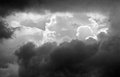 Black and white image of layered clouds on a stormy day with sunlit layers showing behind dark ones Stock Image