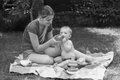 Black and white image of mother feeding her baby at park Royalty Free Stock Photo