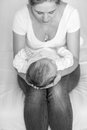 Black and white image of mother sitting on bed and holding her b Royalty Free Stock Photo