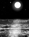 Black and white image of the ocean waves crashing over as the stars shine and the full moon glows in the night sky Royalty Free Stock Image