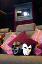 Black and white masks on couch with cushions and projector in movie theater Stock Photos
