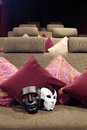 Black and white masks are on soft couch in cozy little movie theater Stock Photos