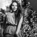 Black-white outdoor portrait of beautiful emotional young brunette woman in stylish dress