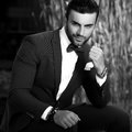 Black-white outdoor portrait of elegant handsome man in classical suit