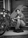 Black and white photo of man maintaining his bicycle Royalty Free Stock Photo