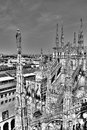 Black and white photo of the marble statues, spires and stone sculptures on the roof of famous Cathedral Duomo and cityscape Royalty Free Stock Photo