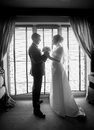 Black and white photo of newlyweds posing against window Royalty Free Stock Photo
